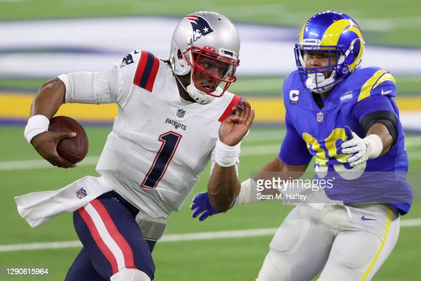 Cam Newton of the New England Patriots rushes the ball past Aaron Donald of the Los Angeles Rams during the second quarter in the game against the...