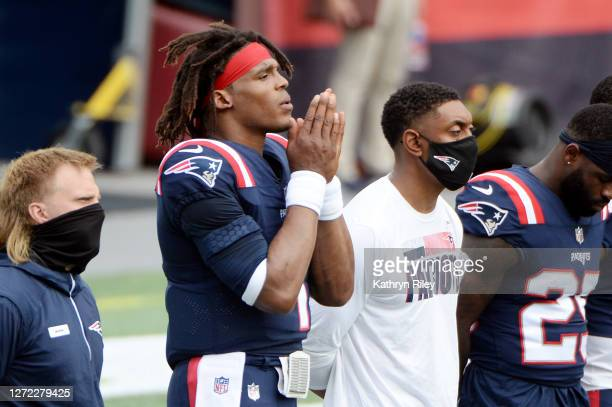 Cam Newton of the New England Patriots stands with teammates as Alicia Keys performs Lift Every Voice and Sing by video stream before the game...