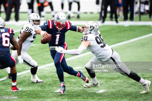 Cam Newton of the New England Patriots wards off Maxx Crosby of the Las Vegas Raiders in the first half at Gillette Stadium on September 27, 2020 in...