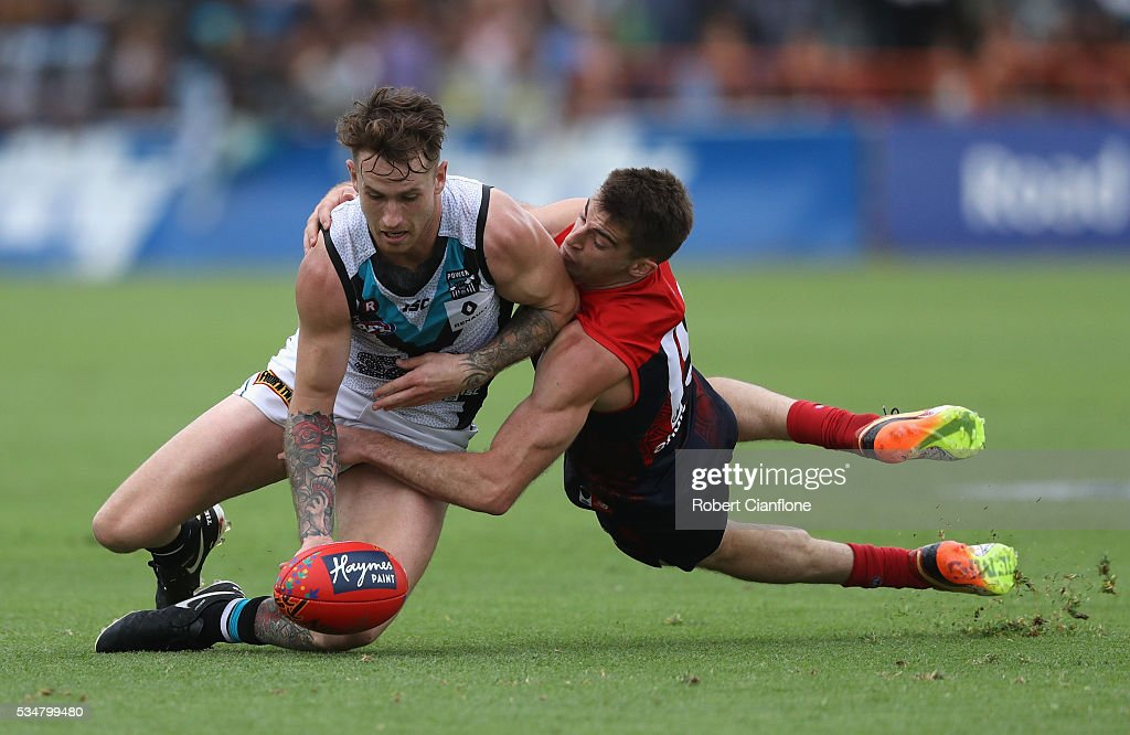 Cam O'Shea of Port Adelaide is tackled by Ben Newton of the Demons during the round 10 AFL match between the Melbourne Demons and the Port Adelaide Power at Traeger Park on May 28, 2016 in Alice Springs, Australia.