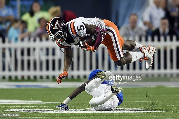Cam Phillips of the Virginia Tech Hokies is tripped up by Kerwin Thomas of the Tulsa Golden Hurricane during the second half of the Camping World...