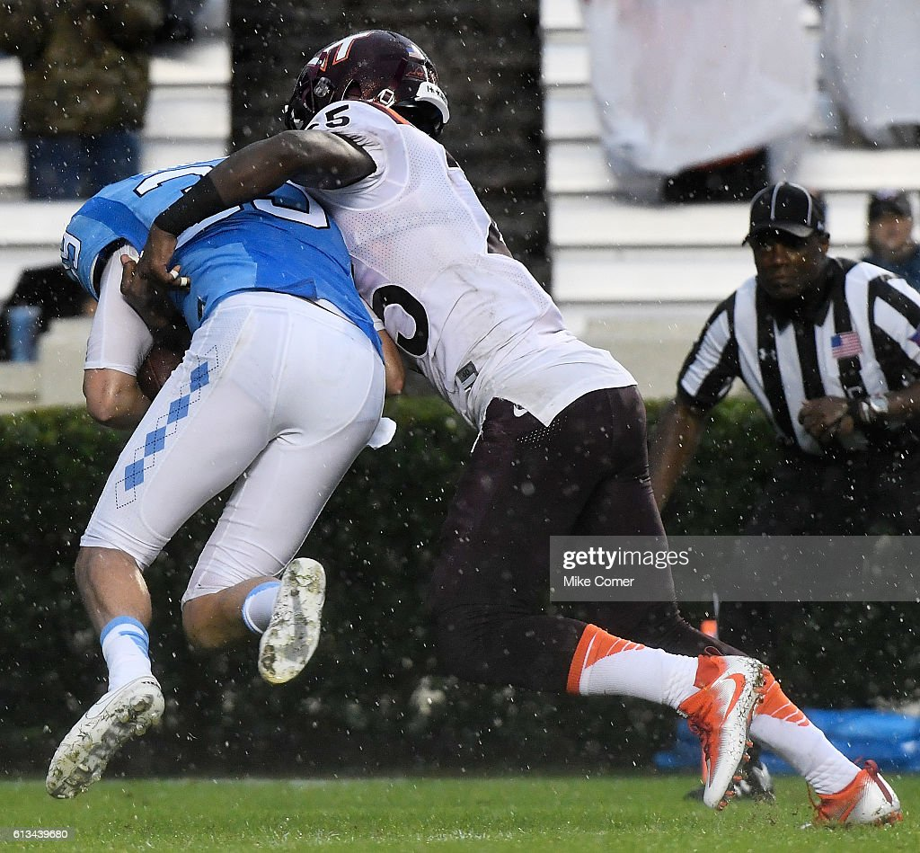 Cam Phillips #25 of the Virginia Tech Hokies tackles Tom Sheldon #39 of the UNC Tar Heels for a turnover at Kenan Stadium on October 8, 2016 in Chapel Hill, North Carolina.
