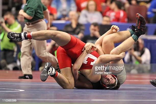 Cam Simaz of the Cornell University Big Red wrestles Ryan Smith of the Cal Poly Mustangs in the 197 pound weight class during the NCAA Wrestling...