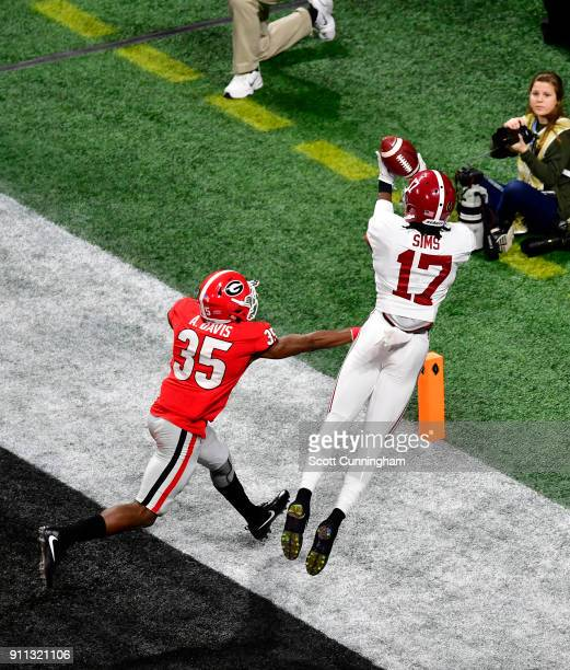 Cam Sims of the Alabama Crimson Tide attempts to make a catch against Aaron Davis of the Georgia Bulldogs in the CFP National Championship presented...