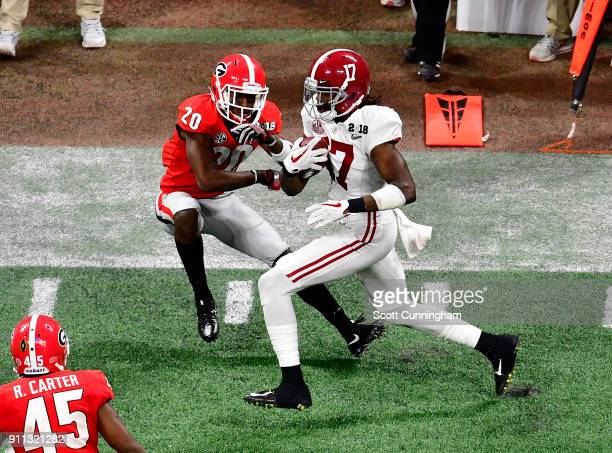 Cam Sims of the Alabama Crimson Tide carries the ball against J R Reed of the Georgia Bulldogs in the CFP National Championship presented by ATT at...