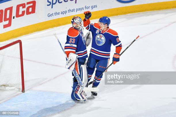 Cam Talbot and Matthew Benning of the Edmonton Oilers celebrate after winning the game against the San Jose Sharks on March 30 2017 at Rogers Place...