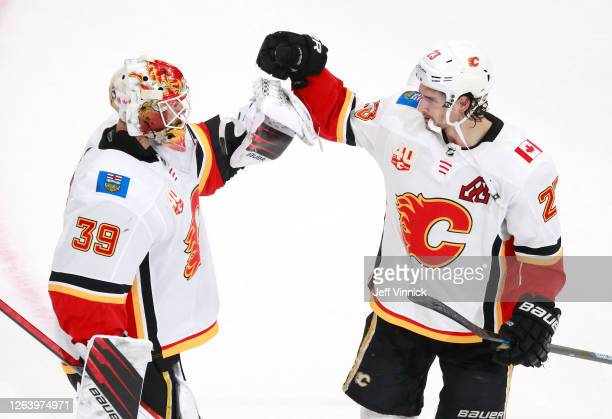 Cam Talbot of the Calgary Flames celebrates the 6-2 win over the Winnipeg Jets with teammate Sean Monahan after Game Three of the Western Conference...