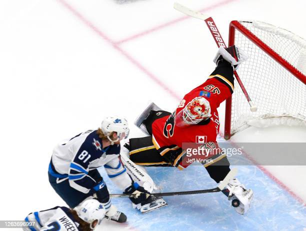 Cam Talbot of the Calgary Flames dives to stop a shot by Kyle Connor of the Winnipeg Jets during Game Two of the Western Conference Qualification...