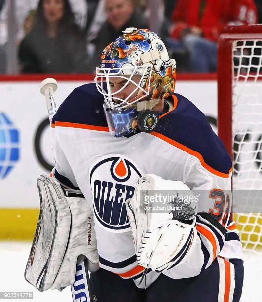 Cam Talbot of the Edmonton Oilers makes a save off of his face mask against the Chicago Blackhawks at the United Center on January 7 2018 in Chicago...