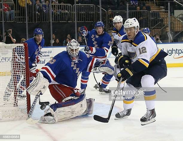 Cam Talbot of the New York Rangers kicks aside a first period shot as Jori Lehtera of the St Louis Blues looks for the rebound at Madison Square...