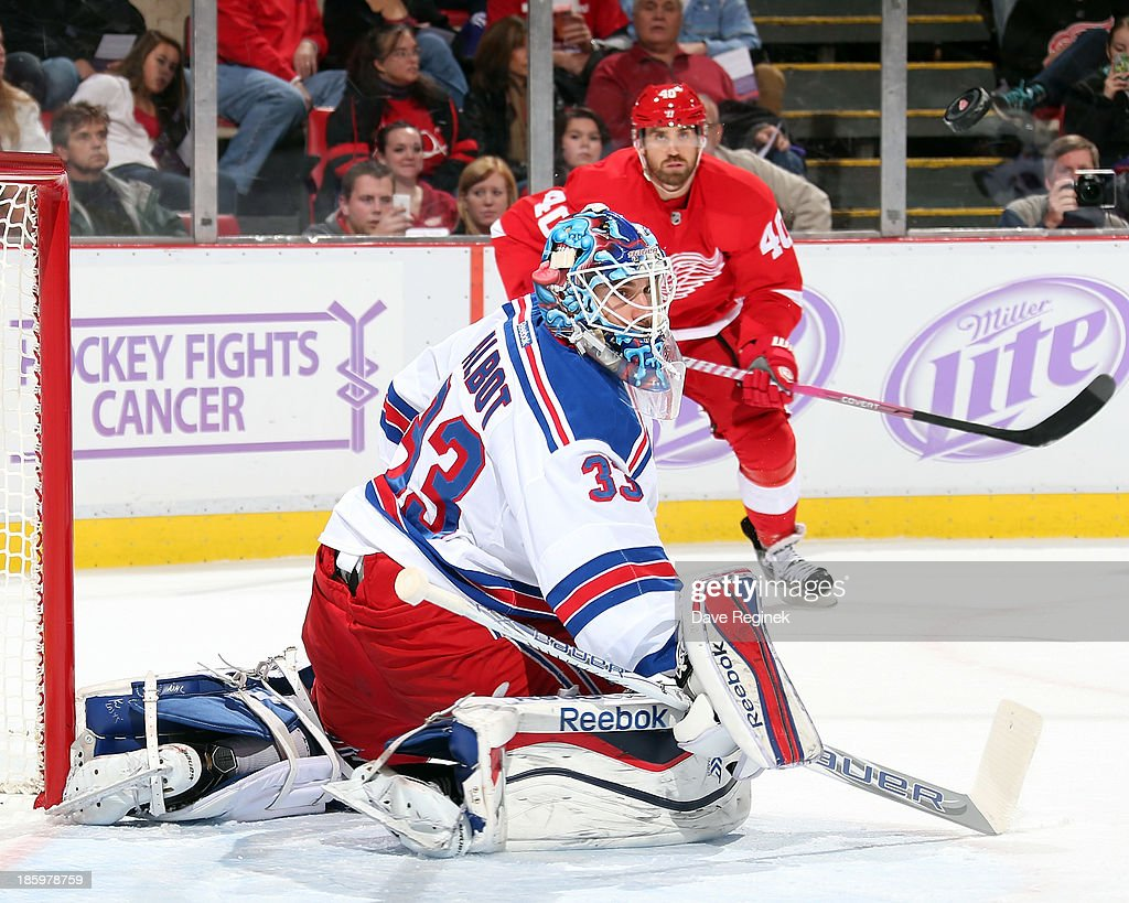 Cam Talbot #33 of the New York Rangers makes a save as Henrik Zetterberg #40 of the Detroit Red Wings follows the play during an NHL game at Joe Louis Arena on October 26, 2013 in Detroit, Michigan. The Rangers win in O