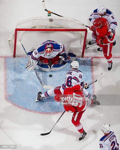 Cam Talbot of the New York Rangers makes a save as teammates Marc Staal and Dan Girardi battle in front with Johan Franzen and Stephen Weiss of the...