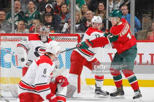 Cam Ward and Brock McGinn of the Carolina Hurricanes defend against Joel Eriksson Ek of the Minnesota Wild during the game on April 4 2017 at the...