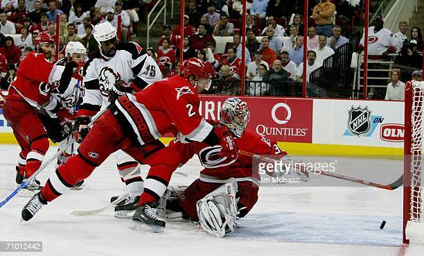 Cam Ward and Glen Wesley of the Carolina Hurricanes reach back to save a goal as Mike Grier of the Buffalo Sabres looks on in game two of the Eastern...