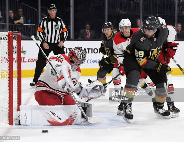 Cam Ward of the Carolina Hurricanes blocks a shot as Alex Tuch of the Vegas Golden Knights waits for a rebound during the second period of their game...