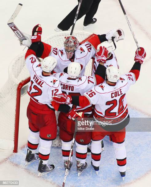 Cam Ward of the Carolina Hurricanes celebrates with teammates Eric Staal Erik Cole and Joe Corvo after defeating the New Jersey Devils 43 in Game...