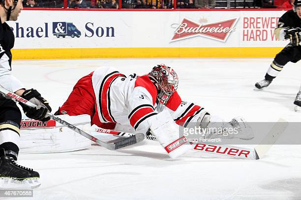 Cam Ward of the Carolina Hurricanes covers up the puck during an NHL game against the Pittsburgh Penguins at PNC Arena on March 26 2015 in Raleigh...