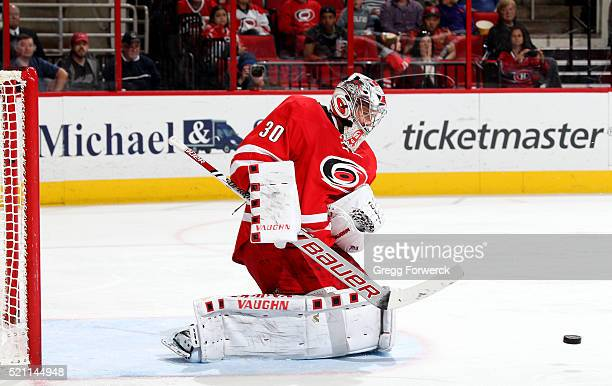 Cam Ward of the Carolina Hurricanes deflects a puck away from the crease during an NHL game against the Montreal Canadiens at PNC Arena on April 7...