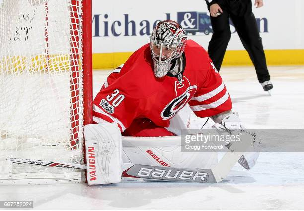 Cam Ward of the Carolina Hurricanes goes down in the crease to hug the pipe and protect the net during an NHL game against the St Louis Blues on...
