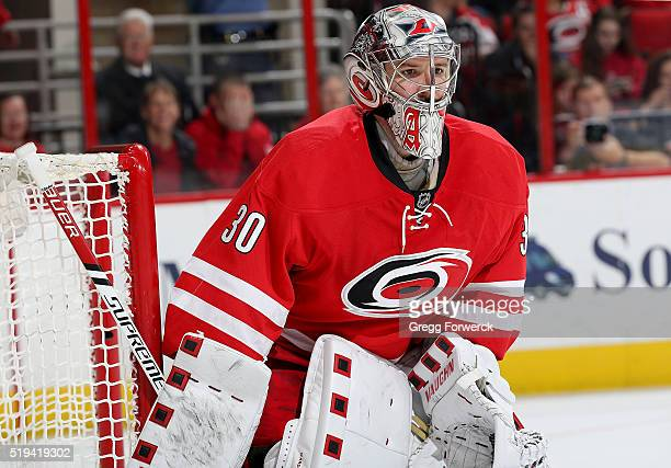 Cam Ward of the Carolina Hurricanes hugs the pipe and keeps his eye on the puck to protect the net during an NHL game against the New Jersey Devils...