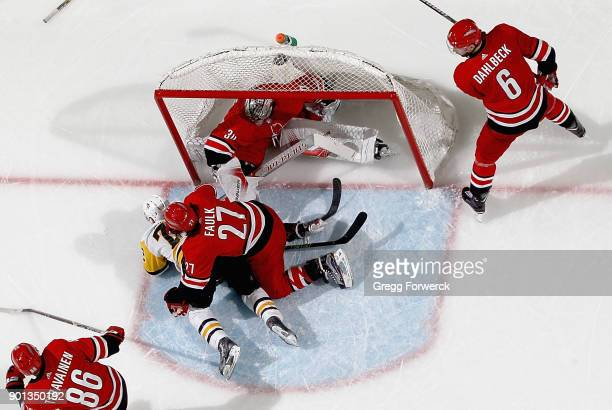 Cam Ward of the Carolina Hurricanes is driven into the back of the net as Patric Hornqvist of the Pittsburgh Penguins is checked to the ice by Justin...