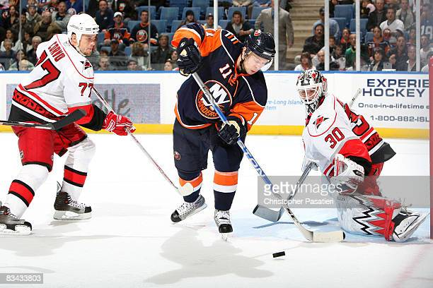 Cam Ward of the Carolina Hurricanes looks to stop a shot on goal by Andy Hilbert of the New York Islanders as Joe Corvo of the Carolina Hurricanes...