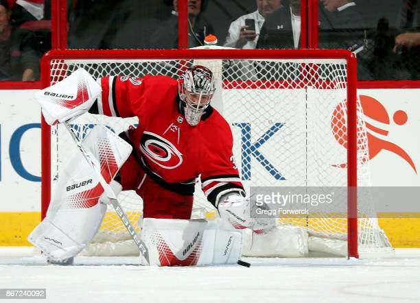 Cam Ward of the Carolina Hurricanes lunges to cover a loose puck during an NHL game against the St Louis Blues on October 27 2017 at PNC Arena in...