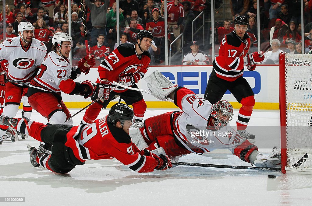 Cam Ward #30 of the Carolina Hurricanes makes a diving save against Bobby Butler #9 of the New Jersey Devils late in the third period during the game at the Prudential Center on February 12, 2013 in Newark, New Jersey. The Hurricanes defeated the Devils 4-2.