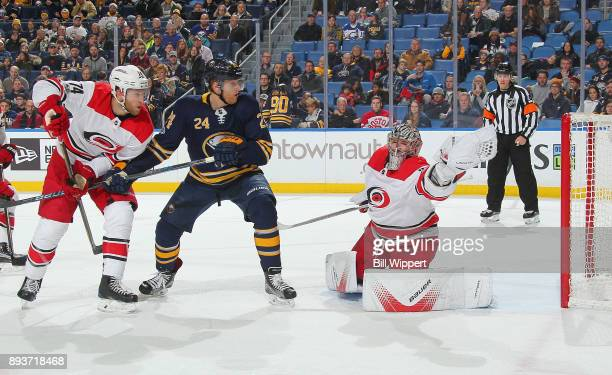 Cam Ward of the Carolina Hurricanes makes a glove save as Hudson Fasching of the Buffalo Sabres and Jaccob Slavin look on during an NHL game on...