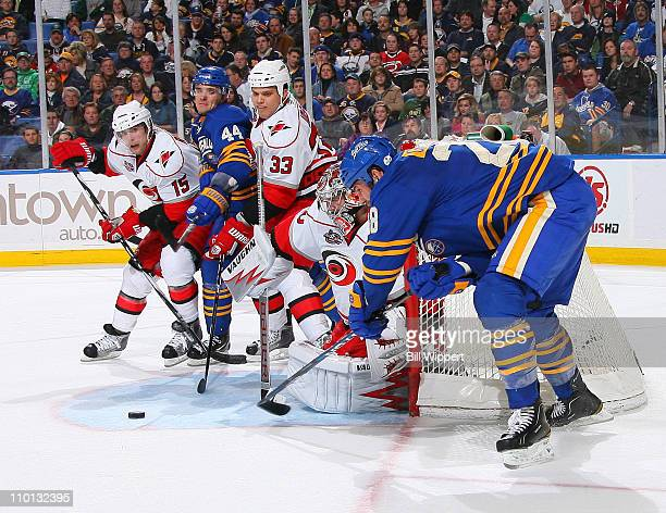 Cam Ward of the Carolina Hurricanes makes a save against Paul Gaustad of the Buffalo Sabres as Andrej Sekera of the Sabres is blocked by Tuomo Ruutu...