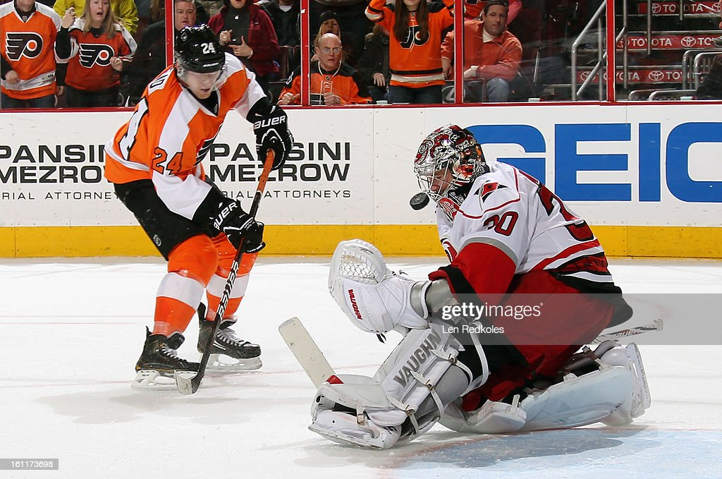 Cam Ward #30 of the Carolina Hurricanes makes a save on Matt Read #24 of the Philadelphia Flyers late in the third period on February 9, 2013 at the Wells Fargo Center in Philadelphia, Pennsylvania. The Flyers went on to defeat the Hurricanes 4-3 in OT.
