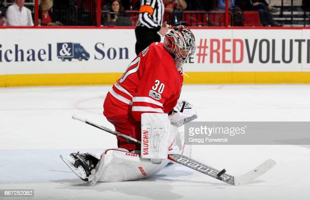 Cam Ward of the Carolina Hurricanes paddles a puck away from the crease during an NHL game against the St Louis Blues on April 8 2017 at PNC Arena in...