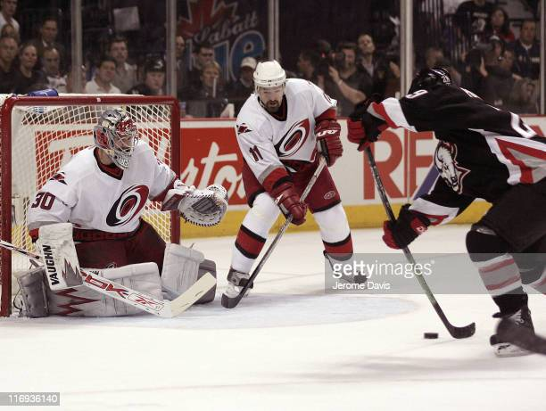 Cam Ward of the Carolina Hurricanes prepares to make a save while teammate Justin Williams waits for the rebound off of Sabres' Jason Pominville...