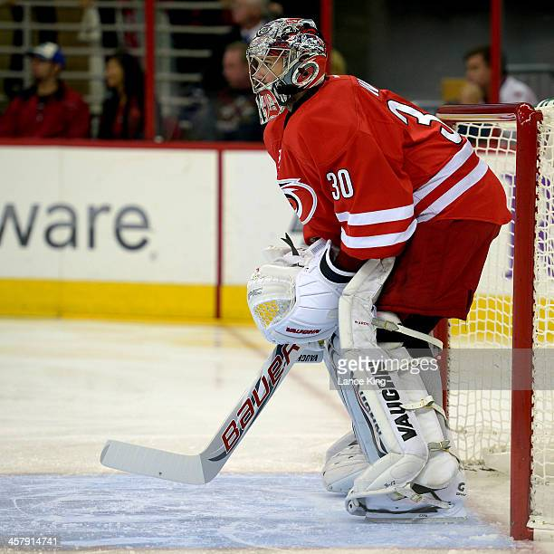 Cam Ward of the Carolina Hurricanes protects the net against the San Jose Sharks at PNC Arena on December 6 2013 in Raleigh North Carolina