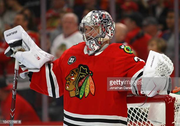 Cam Ward of the Chicago Blackhawks shows a patch on his jersey honoring Stan Mikita during the regular seasopn opening home game against the Toronto...