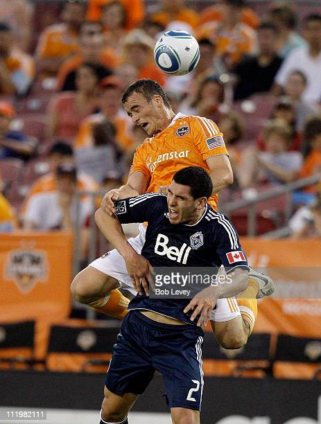 Cam Weaver of the Houston Dynamo goes over the top of Michael Boxall of the Vancouver Whitecaps for a header in the second half at Robertson Stadium...