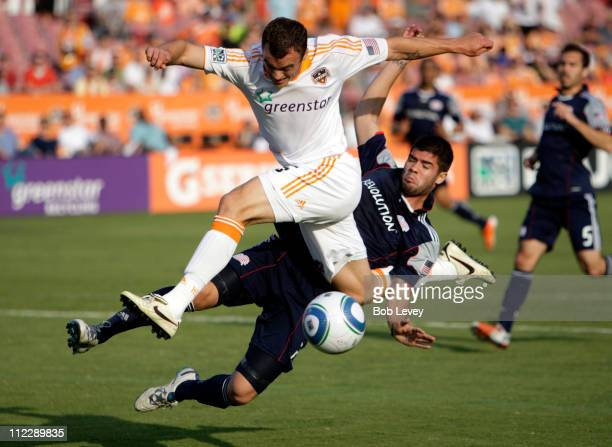 Cam Weaver of the Houston Dynamo is tackled from behind by Franco Coria as he attempts a shot on goal in the first half at Robertson Stadium on April...