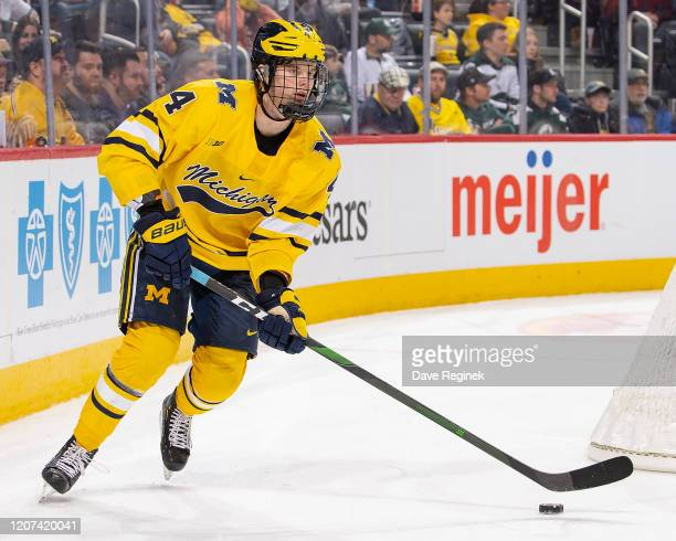 Cam York of the Michigan Wolverines skates around the net with the puck against the Michigan State Spartans during the second period of the annual...