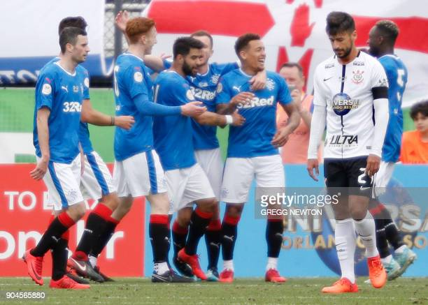 Camacho the dejected captain of Brazilian club Corinthians walks away while players of Scottish club Rangers FC celebrate a second half goal during...