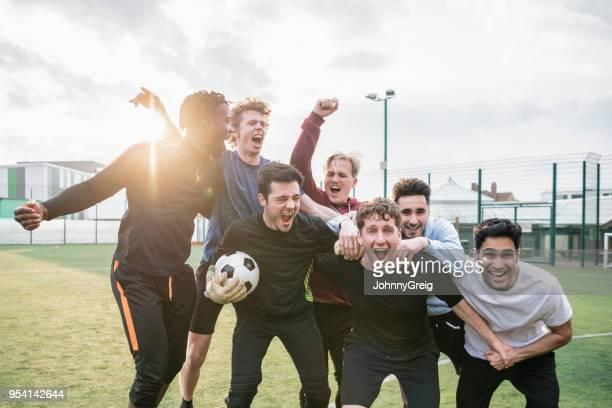 kameradschaft unter freunde jubeln nach dem siegreichen fußballspiel - mannschaftssport stock-fotos und bilder