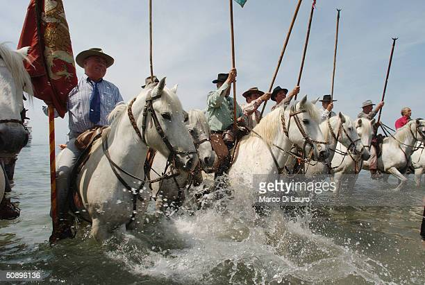 Camargue guardians on horseback accompany the statue of Sara the Black into the sea in Saintes Maries de la Mer in the Camargue region of Southern...