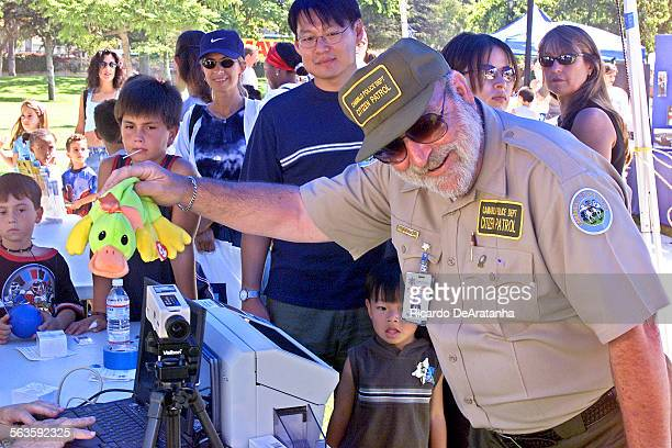 Camarillo Citizen Patrol volunteer David Fish shaking a stuffed animal to attract the attention of a child whose picture is being taken for a new...