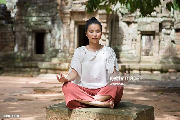 cambodia, angkor, siem reap, young woman practicing yoga in front of ta som temple - kambodschanische kultur stock-fotos und bilder