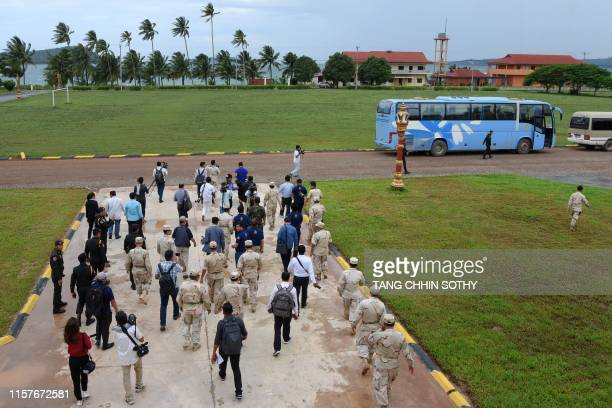 Cambodia naval personnel walk with journalists during a government organised media tour to the Ream naval base in Preah Sihanouk province on July 26...