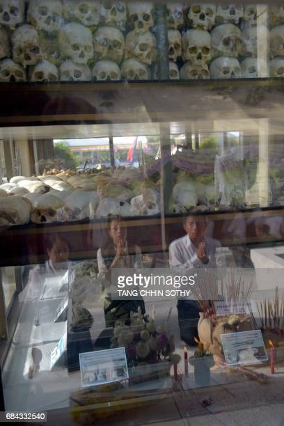 Cambodia people reflect from the glass as they pray in front of skulls at the Choeung Ek killing fields memorial in Phnom Penh on May 18 2017 More...