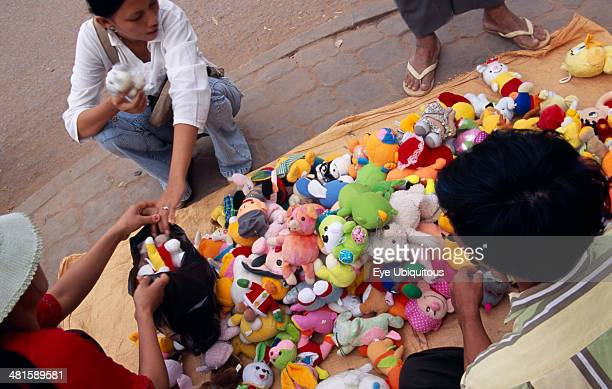 Cambodia Siem Reap Woman buying from a pavement vendor with a display of soft toys for sale