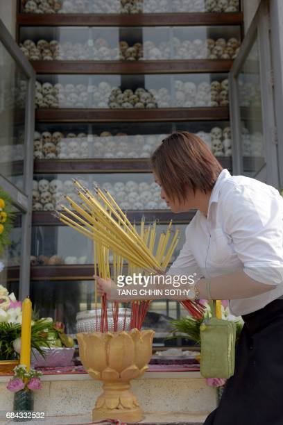 A Cambodia woman prays in front of skulls at the Choeung Ek killing fields memorial in Phnom Penh on May 18 2017 More than 1000 people watched...