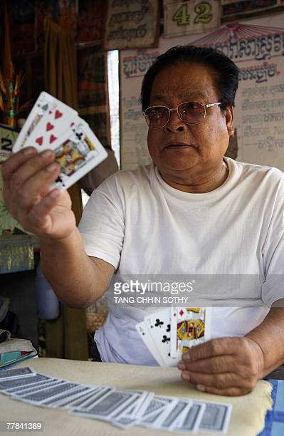 Cambodiacultureastrologyyouth by Suy Se Cambodian fortune teller Him Samrang shows cards to a customer at his shop near Wat Phnom down town Phnom...