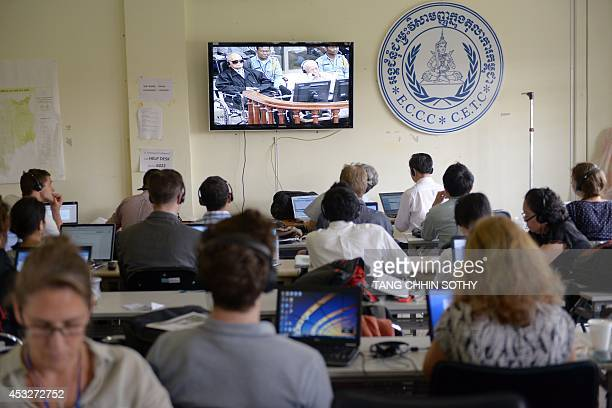 Cambodian and international journalists watch a live video feed showing former Khmer Rouge leader 'Brother Number Two' Nuon Chea and former Khmer...