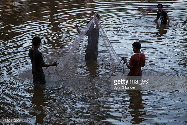Cambodian boys net fishing on the Tonle Sap Lake an estuary of the Mekong River near Siem Reap Cast nets also called throw nets are made up of a...